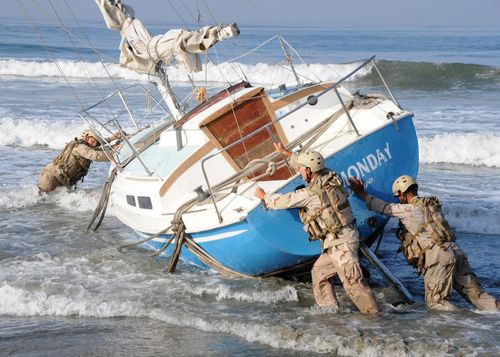 US_Navy_090917-N-1424C-384_Sailors_assigned_to_Beach_Master_Unit_(BMU)_1_move_a_beached_sailboat_into_position_to_be_salvaged_off_the_military_beach