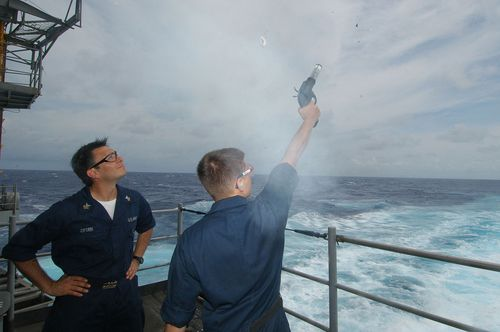 Sailor_fires_a_flare_gun_off_the_fantail