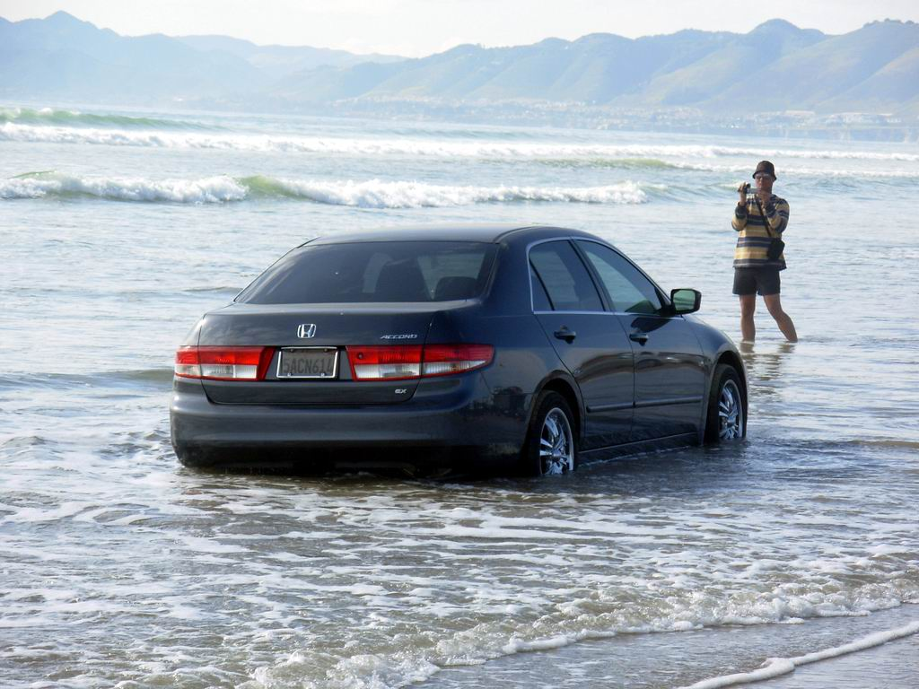 Car caught on beach at high tide.